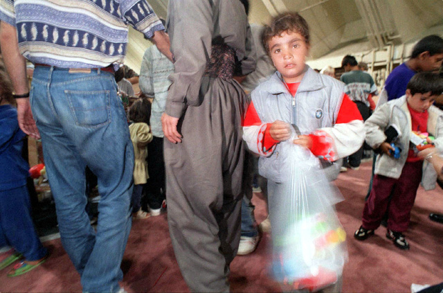A Kurdish boy holds a bag of toys given to him upon arrival at Anderson Air Force Base, Guam, following an almost 17 hour flight from southern Turkey. Operation PACIFIC HAVEN represents a series of airlifts designed to provide sanctuary for some 2,400 refugees fleeing Iraq. Many are considered traitors by the Iraqi Government for working with the CIA-funded Iraqi National Congress and international humanitarian agencies. The Kurds will be housed at Andersen AFB, while they go through the immigration process for residence in the United States