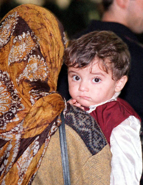 A Kurdish boy waits with his mother during immigration processing at Anderson Air Force Base, Guam, following an almost 17 hour flight from southern Turkey. Operation PACIFIC HAVEN represents a series of airlifts designed to provide sanctuary for some 2,700 refugees fleeing Iraq. Many are considered traitors by the Iraqi Government for working with the CIA-funded Iraqi National Congress and international humanitarian agencies. The Kurds will be housed at Andersen AFB, while they go through the immigration process for residence in the United States