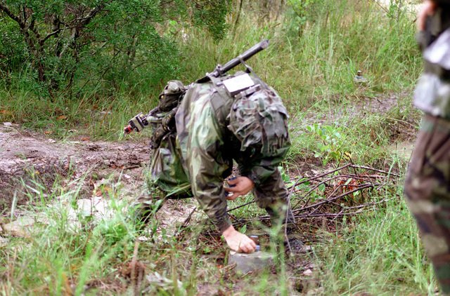 A soldier in full camouflage dress sets a mine field at the Joint Readiness Training Center. The mine is a M17, anti-personnel practice mine that will emit smoke when initiated