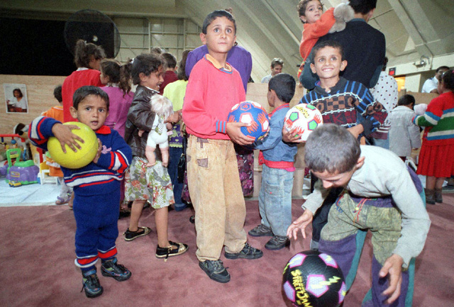 Kurdish children excitedly look through toys upon their arrival at Andersen Air Force Base, Guam, following an almost 17 hour flight from Turkey. The toys were provided for the children through donations by the Salvation Army Guam Corps, the American Red Cross, the Navy/Marine Corps Relief Society, various religious charities and military and civilian private donors. Operation PACIFIC HAVEN represents a series of airlifts designed to provide sanctuary for some 2,400 refugees fleeing Iraq. Many are considered traitors by the Iraqi Government for working with the CIA-funded Iraqi National Congress and international humanitarian agencies. The Kurds will be housed at Andersen AFB, while they...