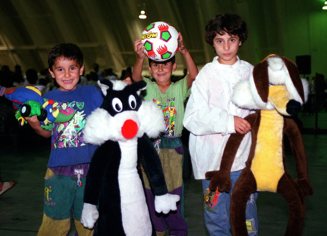 Kurdish children proudly show off some of their new founded American friends. Toys have been generously donated from numerous organization affiliated with military bases and civilian programs in Guam. Operation PACIFIC HAVEN represents a series of airlifts designed to provide sanctuary for some 2,400 refugees fleeing Iraq. Many are considered traitors by the Iraqi Government for working with the CIA-funded Iraqi National Congress and international humanitarian agencies. The Kurds will be housed at Anderson Air Force Base, Guam, while they go through the immigration process for residence in the United States