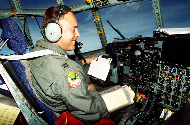 Captain Mike Pinkam pilot and aircraft commander with the 41st Airlift Squadron, Pope Air Force Base, North Carolina has a laugh during his flight to Tuzla Air Base. The 41st Airlift Squadron fly C-130 aircraft and are deployed to Ramstein Air Base, Germany