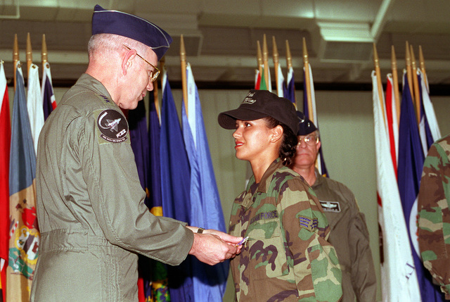GEN. Hawley, ACC commander, smiles as he pins a Purple Heart on SENIOR AIRMAN Nicole Van Name, 509th Comptroller Squadron. She was wounded in the bombing of Kobar Towers in Dhahran, Saudi, Arabia