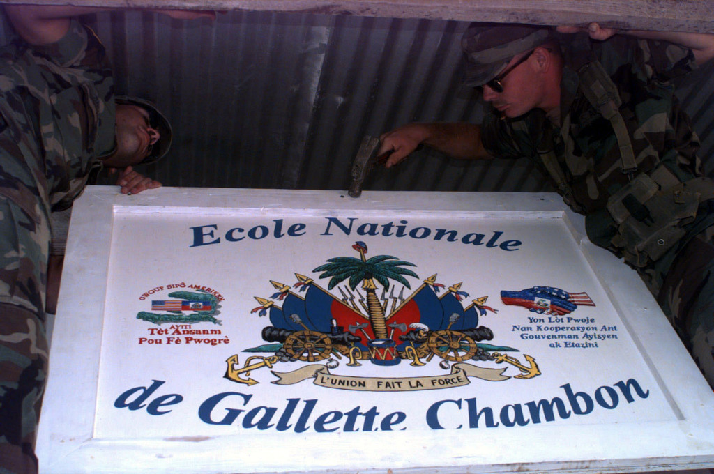 US Army Soldiers from Alpha Company, 864th Engineers Fort Lewis, WA put the finishing touches on Chambon School in Gallette Chambon, Haiti, by putting up the Schools sign. The 864th Engineers rebuilt the school during Operation FARIWINDS 96