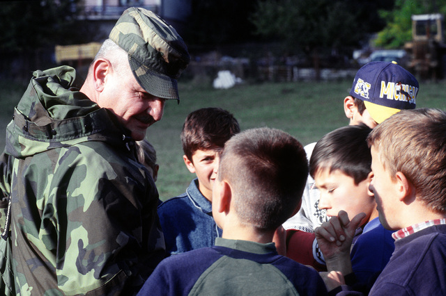 U.S. Army SGT. MAJ. Jim Parker of the Implementation Force (IFOR) Campaign Task Force talks with the local children of Pale during the band concert sponsored by the Commander in CHIEF, Naples, Italy