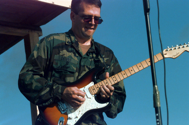 US Navy PETTY Officer 2nd Class Scott Davis, a member of the Commander In CHIEF South Band, gets into his guitar part while entertaining locals in the town of Pale, Bosnia and Herzegovina, during Operation JOINT ENDEAVOR