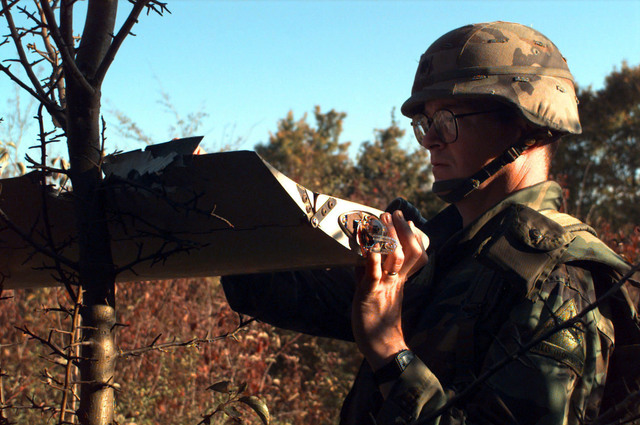 A close up left side view of US Army LTC David M. Kennedy Division Artillery Brigade (DIVARTY) Executive Officer, as he examines the wing from the wreckage of a Unmanned Aerial Vehicle (UAV), which lay on a hillside in the Russian sector of the Multinational Division North (MDN). The wing apparently struck a tree and broke off on impact