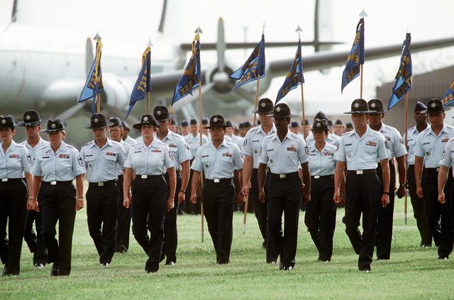Basic training instructors and staff march during a