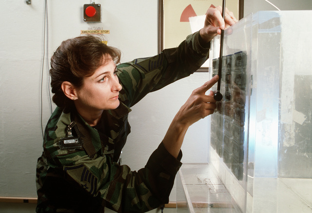 MASTER SGT. Jocelyn Nixon measures a radiation level at the Armstrong Laboratory Occupational and Health Directorate where she is the superintendent of the instrument calibration facility. She is wearing a collar badge to gauge doses of radiation to the thyroid. Nixon works primarily with the air Force Dosimetry Program which distributes, collects, and reads radiation badges worn by Air Force X-ray workers in the medical, dental, and industrial fields. Published in AIRMAN Magazine October 1996