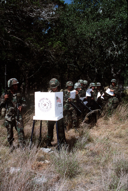 Members of the United States Air Force with their ballots in hand, are ready to exercise their freedom to vote under field conditions. Published in AIRMAN Magazine October 1996
