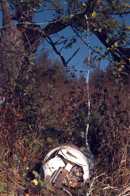 The wreckage of a Predator Unmanned Aerial Vehicle (UAV) lays on a hillside in the Russian sector of the Multinational Division North (MDN) area of operations. Wiring hangs in the trees and the camera assembly lay on the ground