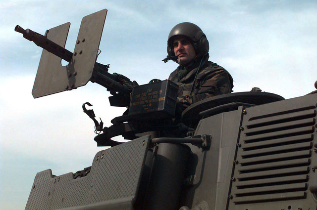 A crewmember, armed with a 7.62mm turret machine gun, stands up through the port side turret hatch of an Italian Army 19th Cavalry Regiment Consortium IVECO - OTO Melara Centauro B1 (8x8) Tank Destroyer. The Italian Army is in Bosnia during Operation Joint Endeavor, which is a peacekeeping effort by a multinational Implementation Force (IFOR), comprised of NATO and non-NATO military forces, deployed to Bosnia in support of the Dayton Peace Accords