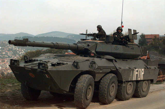 An IFOR marked Italian Army 19th Cavalry Regiment Consortium IVECO - OTO Melara Centauro B1 (8x8) Tank Destroyer is parked on the shoulder of a road while on patrol in Sarajevo, Bosnia-Herzegovina. Three crewmembers are seen standing up through the two turret hatches and the driver's hatch. The Italian Army is in Bosnia during Operation Joint Endeavor, which is a peacekeeping effort by a multinational Implementation Force (IFOR), comprised of NATO and non-NATO military forces, deployed to Bosnia in support of the Dayton Peace Accords