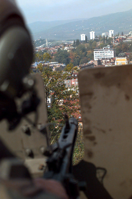 Long shot view of Sarajevo, Bosnia-Herzegovina, seen through the aiming port of a protective metal plate attached to a 7.62mm turret machine gun attached to the turret of an Italian Army 19th Cavalry Regiment Consortium IVECO - OTO Melara Centauro B1 (8x8) Tank Destroyer. The Italian Army is in Bosnia during Operation Joint Endeavor, which is a peacekeeping effort by a multinational Implementation Force (IFOR), comprised of NATO and non-NATO military forces, deployed to Bosnia in support of the Dayton Peace Accords