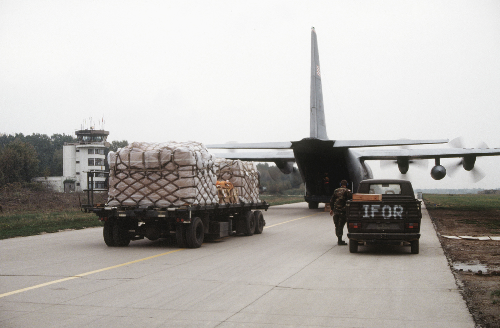 Air Transportation personnel from the 621st Aerial Port Squadron, McGuire Air Force Base, New Jersey, wait for the signal to load up three pallets onto a C-130 transport aircraft from the 41st Airlift Squadron, Pope Air Force Base, North Carolina. The Air Transportation Specialists are temporarily assigned to the 4100th Group (Provisional)