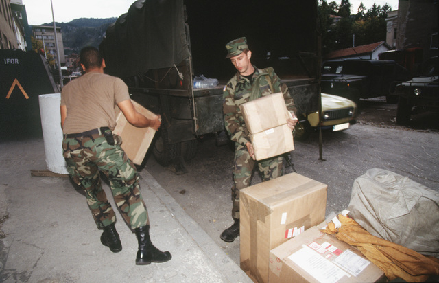 SENIOR AIRMAN Raymond Lahti, 4100 Group (Provisional) Postal Service, from Woodhaven, Michigan and Sergeant Winston Johnson, Sarajevo Postal Company take registered mail packages off a truck in Sarajevo so they can be signed over to Army postal clerks