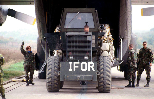 Three 4100th Group Provision (USAF) personnel help guide an IFOR marked military forklift wheeled loader in loading palletized cargo onto a Swedish Air Force C-130 at Tuzla Air Base, Bosnia-Herzegovina. These three are A1C Tracey Montgomery (621st Aerial Port Squadron), 1LT Steve Jacque, and SRA Shain Grass (621st Aerial Port Squadron), and they are in Bosnia participating in Operation Joint Endeavor. Operation Joint Endeavor is a peacekeeping effort by a multinational Implementation Force (IFOR), comprised of NATO and non-NATO military forces, deployed to Bosnia in support of the Dayton Peace Accords