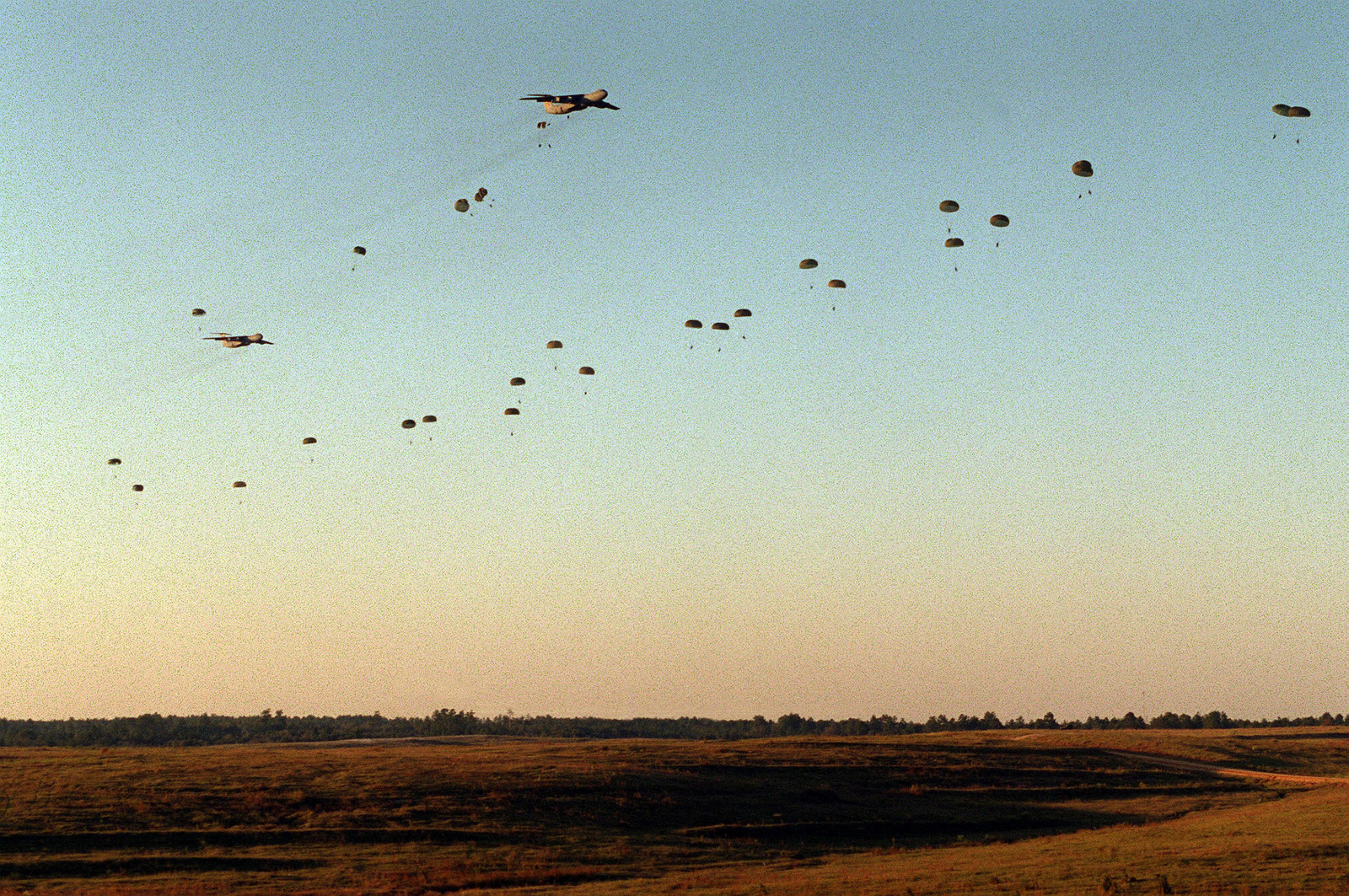 The sky rains paratroopers as soldier from the 82nd Airborne Division jump from a US Air Force C-141 Starlifter into the Joint Readiness Training Center (JRTC)