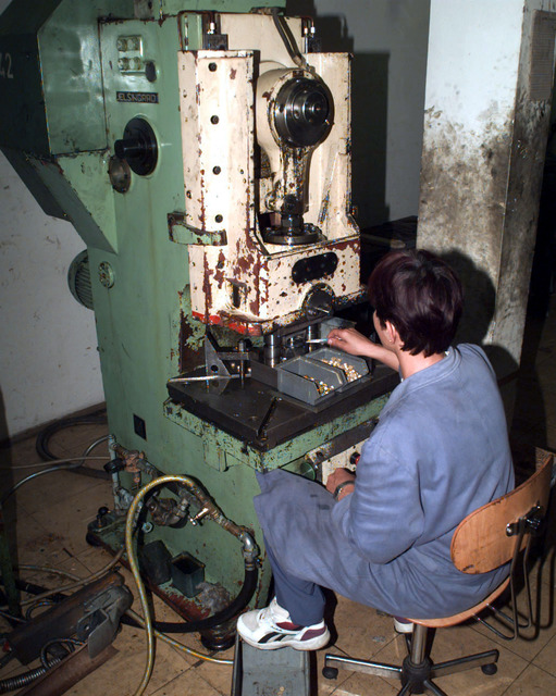 A Close up view of a female factory worker operating a stamping machine used to process ammunition casings, at the ammunition factory in Doboj, Bosnia-Herzegovina