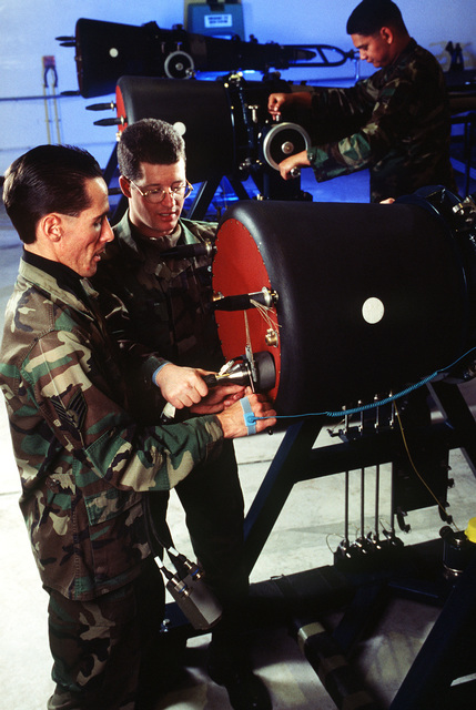 Nuclear Weapons Maintenance Technicians STAFF SGT. Kenneth Shires (left) and SENIOR AIRMAN Jeff Sodano (middle), of the 90th MXS/LGMWP, install a W5A cable on a Peacekeeper Reentry Vehicle located in the Weapons Storage Area. The W5A cable is the main interface between the missile and the R.V