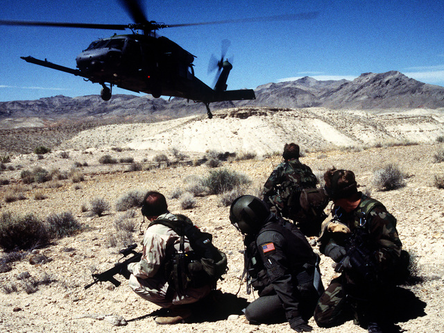 An HH-60G from the 66th Rescue Squadron, Nellis AFB, Nev., flies in above pararescue members for pick-up during a training mission in the ranges north of Nellis