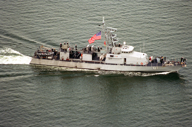 Aerial port beam view of the coastal patrol craft USS FIREBOLT (PC-10) underway at speed as the vessel returns from a Mediterranean deployment