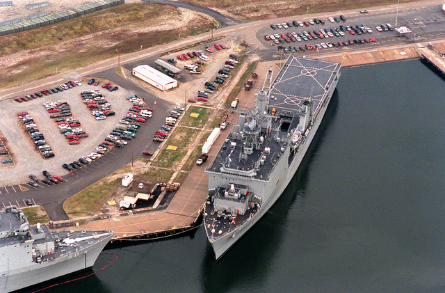 An aerial overhead view of a section of the Naval Amphibious Base Little Creek showing the dock landing ship USS OAK HILL (LSD-51) tied up at the pier. The bow of the USS CARTER HALL (LSD-50) appears in the lower left of the photograph