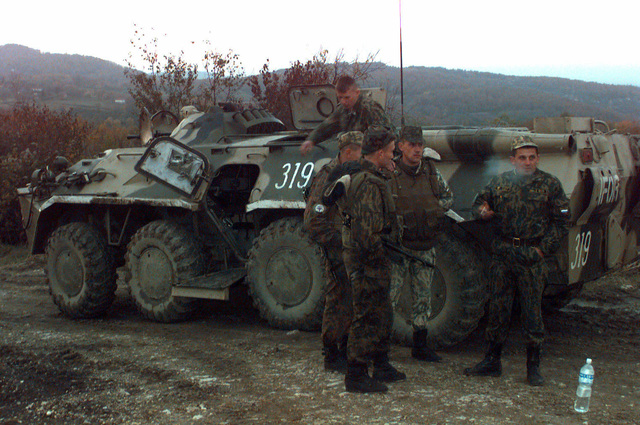 Armed, Russian Army soldiers stnad on and next to their IFOR marked BTR-80 Armored Personnel Carrier (APC) smoking and taking a break while on patrol in a Russian Sector area near Ugljevik, Bosnia-Herzegovina. The Russians are in Bosnia participating in Operation Joint Endeavor, which is a peacekeeping effort by a multinational Implementation Force (IFOR), comprised of NATO and non-NATO military forces, deployed to Bosnia in support of the Dayton Peace Accords