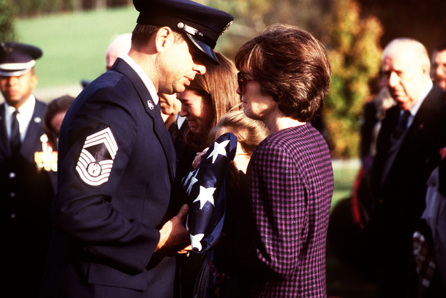"CHIEF MASTER SGT. of the Air Force, David Campanale, presents a folded flag to Donna Eakins, daughter of CHIEF MASTER SGT. of the Air Force (RET) Arthur ""Bud"" Andrews. CMSgt Andrews passed away on 26 Oct 1996 in Marietta, GA., after complications following heart surgery. He was 62 years old"