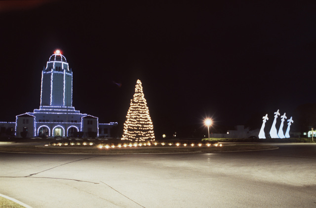 The base Christmas tree is lighted with white lights. Behind the tree, Building 100 (the Taj) is glowing with blue lights