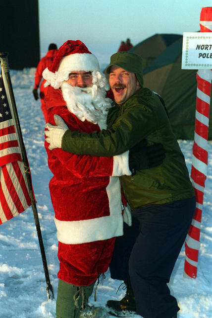 There is always room for a little humor, even in the harsh environment of the North Pole. Navy Sonar Technician First Class Mark Pierce greets everyones favorite holiday figure, Santa Claus. Santa was of course Sonar Technician First Class Robert Bissonnette. Both are crew members assigned to the U.S. Navys attack submarine USS POGY (SSN 647). The U.S. Navys attack submarine USS POGY (SSN 647) returned to Hawaii, on Tuesday, November 12, after a 45-day research mission to the North Pole. The second of five planned deployments through the year 2000, USS POGY embarked a team of researchers led by Mr. Ray Sambrotto of Columbia University. During the several thousand mile trek, the submarine ...