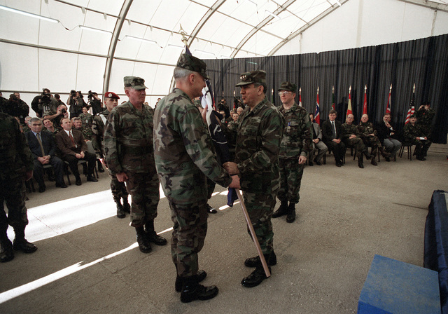 US Army General George A. Joulwan (right), Supreme Allied Commander Europe, passes the Implementation Forces (IFOR) guide on to US Army General William W. Crouch (left), the new commander-in-chief of NATO-led Peace IFOR, signifying the transfer of authority to Allied Land Forces Central Europe. The ceremony was held at the Sarajevo Airport, Bosnia and Herzegovina in support of Operation JOINT ENDEAVOR. Seated in the front row and seen to the left of the military leaders are Presidents Momcilo Krajisnik (left), and Kresimir Zubak (right), of Bosnia and Herzegovina