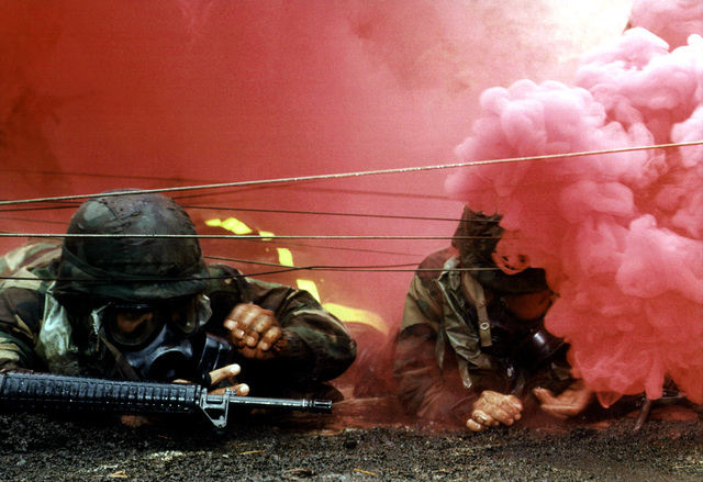 Honorable Mention, Combat Camera Category, 1ST Runner-up Portfolio entry, 1996 Military Photographer of the Year Competition. Title: Down in Smoke. During field training at Camp Fuji, Japan, US Army Specialists (SPCs) Jonathin Carol and Albert Hernandez from Camp Zawa crawl under simulated barbed wire as smoke representing poison gas envelopes them, Tuesday, August 13, 1996