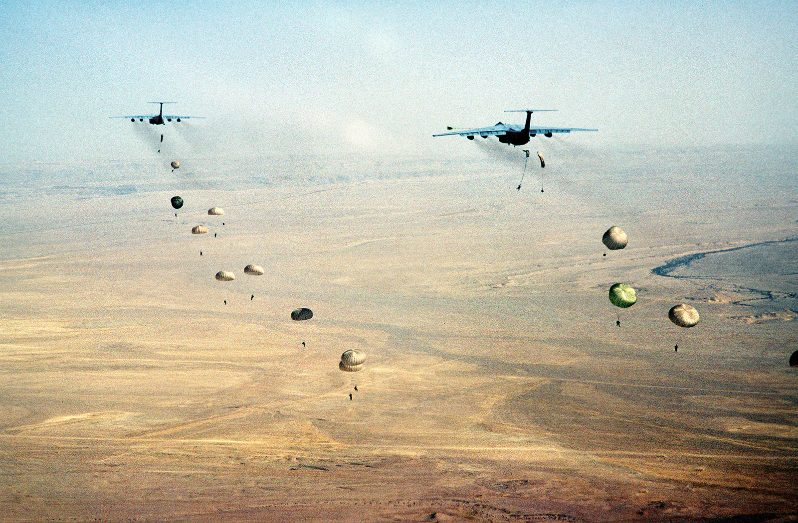 Egyptian Army paratroopers perform static-line jumps out the sides of two C-141B Starlifter aircraft from the 62nd Air Wing, McChord Air Force Base, over the WADI drop zone in Egypt, during the joint United States and Egyptian military exercise