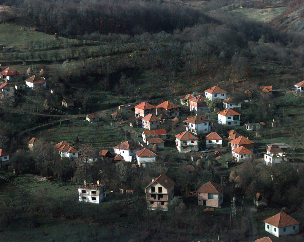 An aerial view showing two-story buildings, some are damaged, in Dugi Dio, Bosnia-Herzegovina