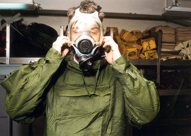 Damage Control Technician Brandon Love dons the MCU-2P gas mask during a chemical and biological training exercise onboard the US Navy nuclear powered aircraft carrier USS ENTERPRISE (CVN 65). The Enterprise is returning to her homeport of Norfolk, VA, after a six-month deployment to the Red Sea during Operation SOUTHERN WATCH. (Duplicate image, see also DNSD0203115 or search 961121N4700G001)