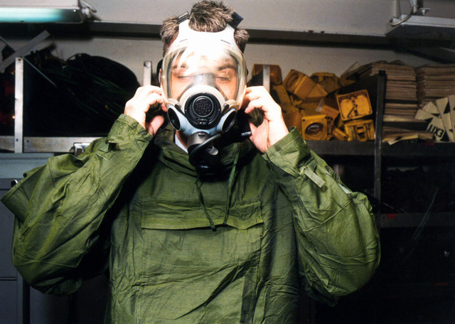 On board the US Navys nuclear-powered aircraft carrier USS ENTERPRISE (CVN 65), Damage Control Fireman Brandon Love properly dons a MCU2P gas mask, used as part of the chemical and biological ensemble. Enterprise, under the operational command of Commander, Fifth Fleet, was operating in the Red Sea in support of Operation SOUTHERN WATCH, and is on her way home to Norfolk, Virginia, from a six month deployment. (Duplicate image, see also DNSD0110010 or search 961121N4700G001)