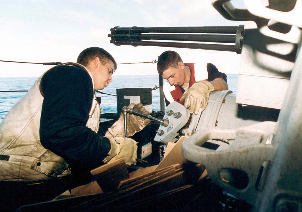 US Navy Fire Control Technician 2nd Class (FC 2) Zenas Haskins (left) and Fire Control Technician 3RD Class (FC 3) Jason Bennett uploads practice-rounds into the 20mm Vulcan Phalanx 6-barrelled (Mk 15) Close-In Weapons System (CWIS), onboard the US Navy aircraft carrier USS KITTY HAWK (CV-63)