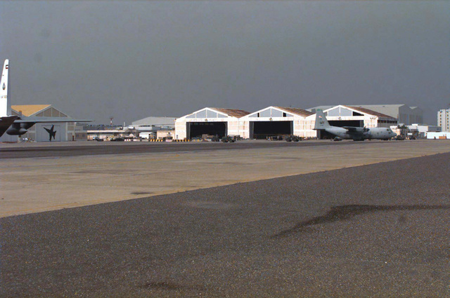 A Moody Air Force Base, Georgia C-130 Hercules is parked in front of Hangar 4 on Tarmac 1. This view is from the intersection of Taxiway E-7 and E-10 looking northwest toward Hangar 4. This portion of ramp is most frequently used by U.S. Air Force aircraft