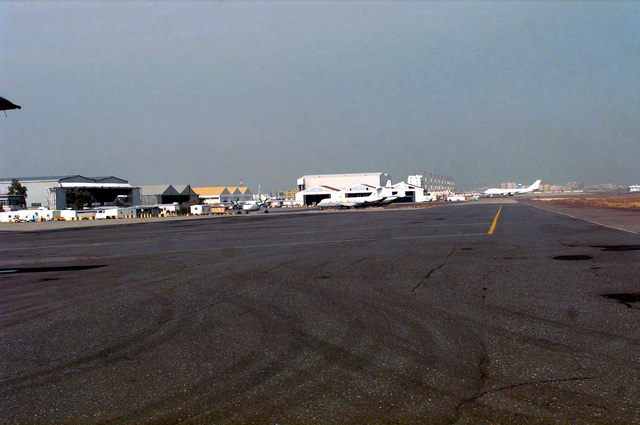 View of the intersection of Taxiway E-6 and E-10 looking north along E-10. This Taxiway will be replaced with concrete and widened eleven meters during the 60 day construction