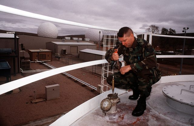 Power Plant Foreman, Technical Sergeant William Bennett, checks the diesel fuel level of one of two 60,000 gallon tanks used to power the three generators at Joint Defense Facility Nurrungar, Australia. TECH. SGT. Bennett is assigned to the 5th Space Warning Squadron which shares responsibility for the operation of the facility with Australia's No. 1 Joint Communications Unit in the Australian interior.Published in AIRMAN Magazine, December 1996. Exact Date Shot Unknown
