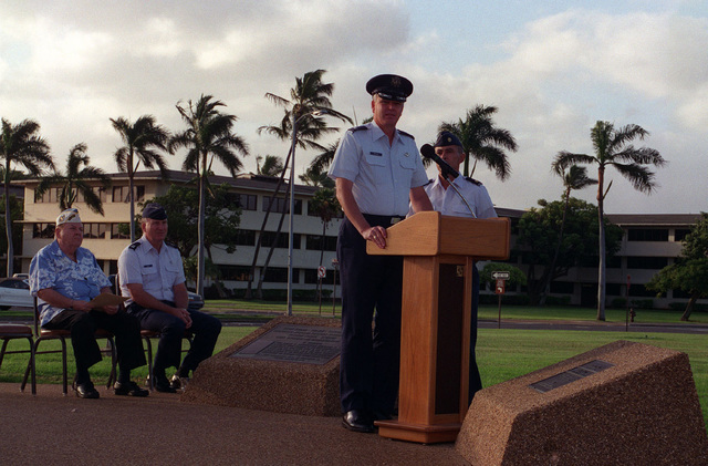 During a twilight ceremony, COL. Bruce Brown, Commander of the 15th Air Base Wing, speaks in memory of those who gave their lives on December 7, 1941. Standing beside COL. Brown is attack survivor Robert May of the 11th Bombardment Wing. Seated in the background are Chaplain Thomas Kelly and MAJ. Joseph Davis