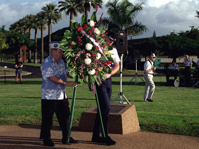 """Mr. Robert May """"survivor of the attack on Pearl Harbor"""" and US Air Force Colonel (COL) Bruce Brown, Commander, 15th Air Base Wing, Hickam AFB, Hawaii carry a wreath at the Hickam AFB Memorial during a twilight ceremony"""