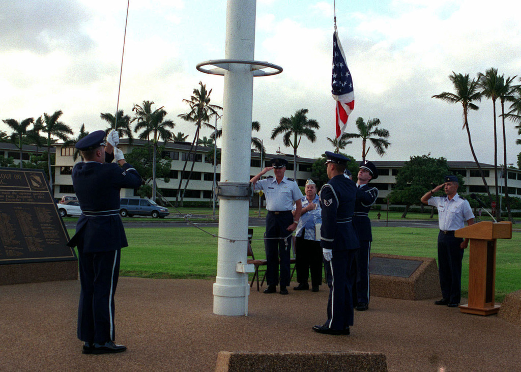 US Air Force Colonel (COL) Bruce Brown, Commander of the 15th Air Base Wing, Hickam AFB, Hawaii, Mr. Robert May a survivor of the attack on Pearl Harbor and USAF Major (MAJ) Joseph E. Davis salute as members of the 15th Air Base Wing Honor Guard raise the Flag during a twilight ceremony held at Hickam Air Force Base