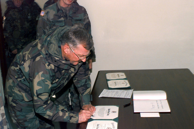 GEN John M. Shalikashvili, CJCS, signs promotion and reenlistment documents in the 1ST Infantry Division Commander's office