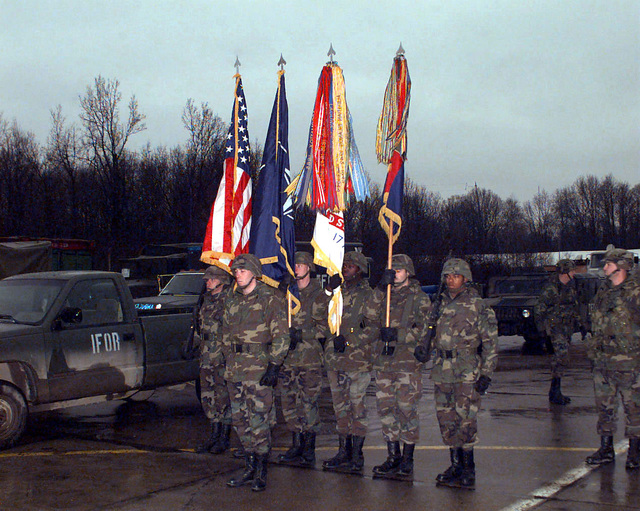 The 1ST Infantry Division Honor Guard stands at attention in a parking lot in front of a CUCV II Type B Truck, with IFOR markings, and other US Army vehicles waiting for the arrival of GEN. Dennis Reimer (USA), CHIEF of STAFF of the Army, to Tuzla Main Base, Bosnia-Herzegovina. GEN. Reimer is visiting US forces involved in Operation Joint Guard, which is a peacekeeping effort by a multinational Implementation Force (IFOR), comprised of NATO and non-NATO military forces, deployed to Bosnia in support of the Dayton Peace Accords