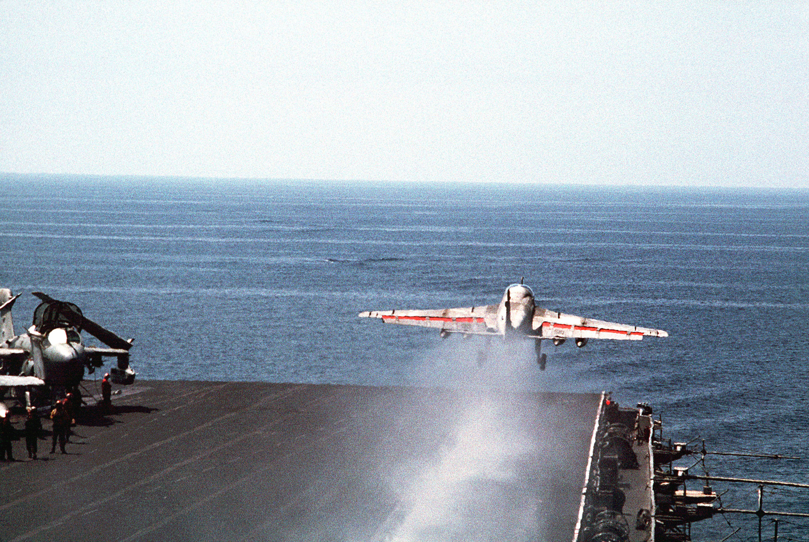 An A-6E Intruder aircraft is launched from the number one starboard catapult of the aircraft carrier USS Independence (CV-62). An EA-6B Prowler aircraft is parked on deck to the left