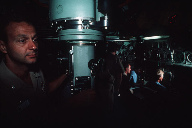 In this dimly lighted view of the interior of the nuclear-powered attack submarine USS Oklahoma City (SSN-723) control room, a Navy commander at the periscope and the bow plane control personnel at their stations have a mystic appearance reflective of the submarine reputation of stealth