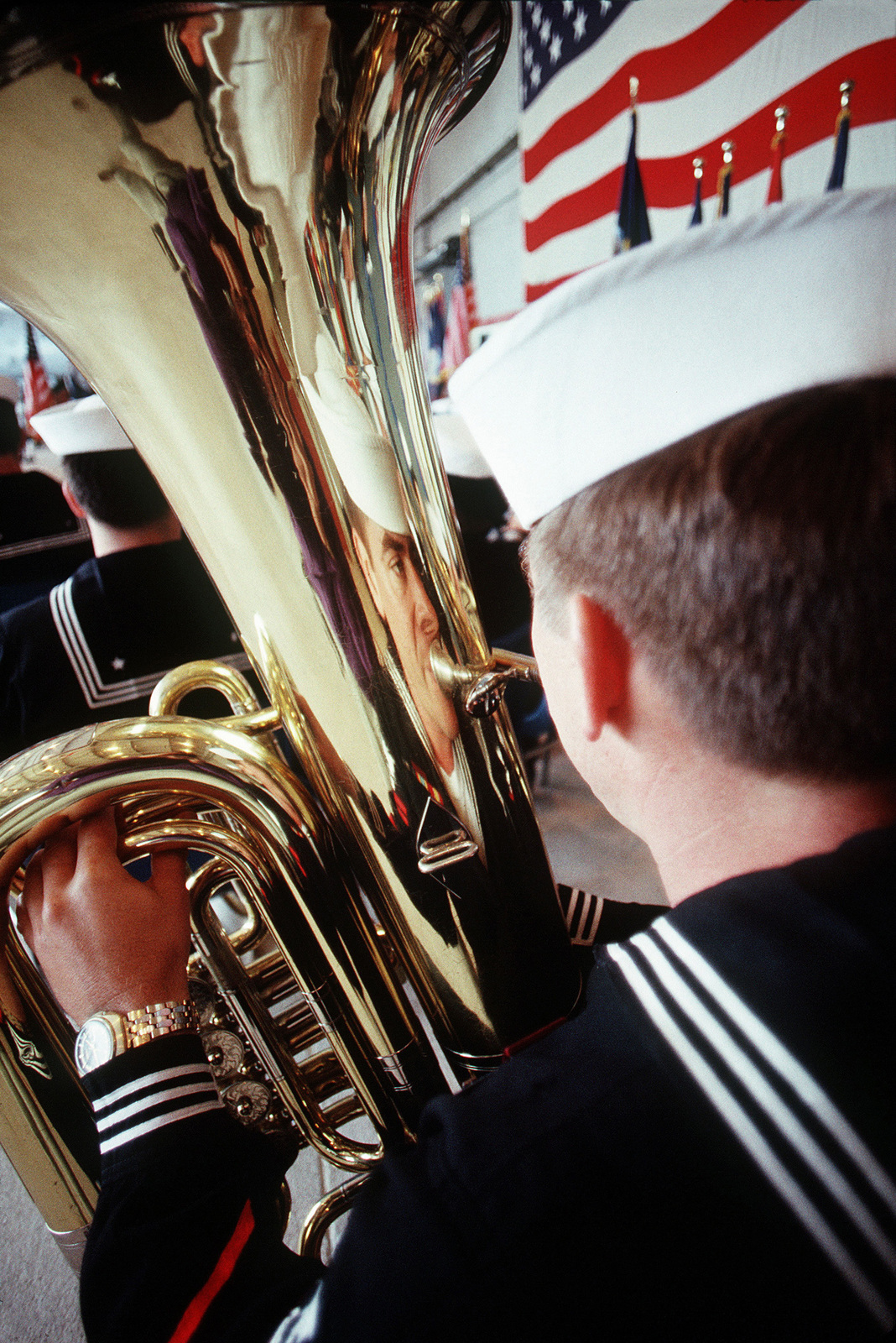 """Navy Photojournalist are taught to look for the """"unusual"""" image. Here, it appears the French Horn player is observing his own reflection in the instrument"""