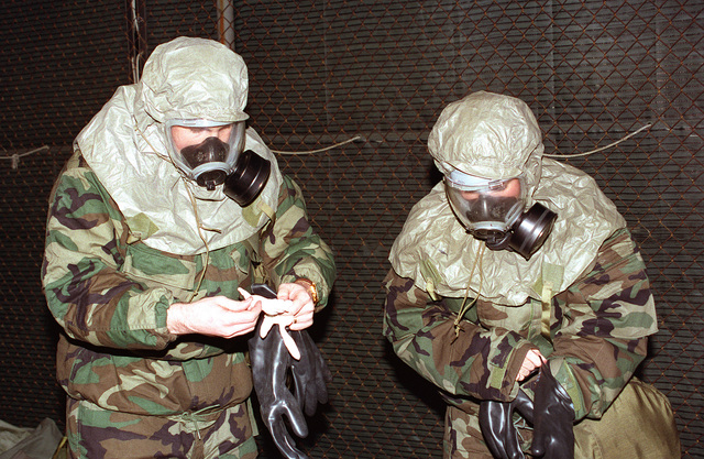 Two airmen from the 61st Air Base Group put on their chemical suits. Exact Date Shot Unknown